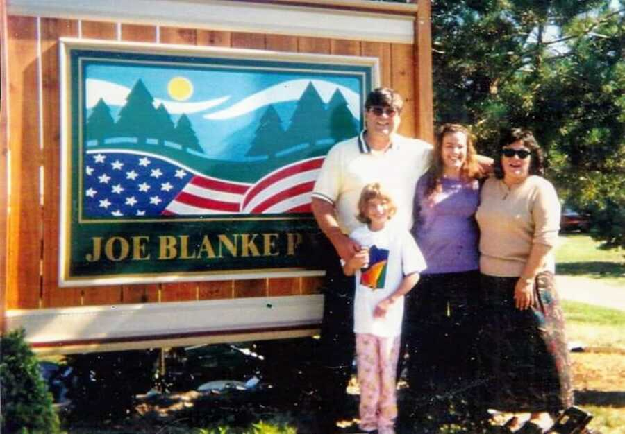Young girl poses with her mom and grandparents in front of Joe Blanke Park sign, the park her grandfather opened and owned before he passed from cancer
