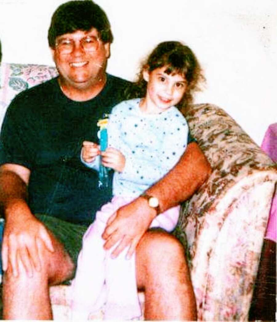 Little girl sits on her grandfather's lap while they smile for a photo together