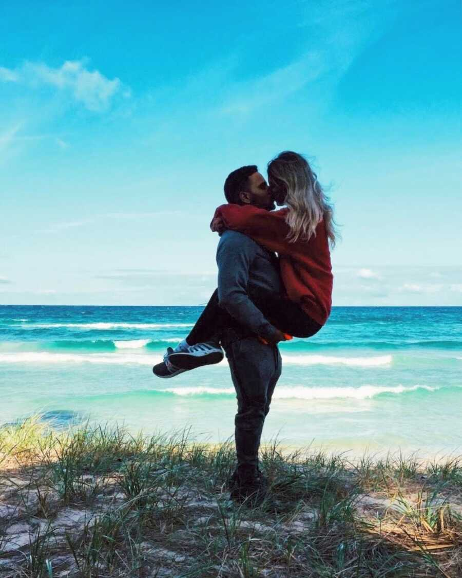 Young man holds his wife while they share an intimate kiss with waves at the beach crashing behind them