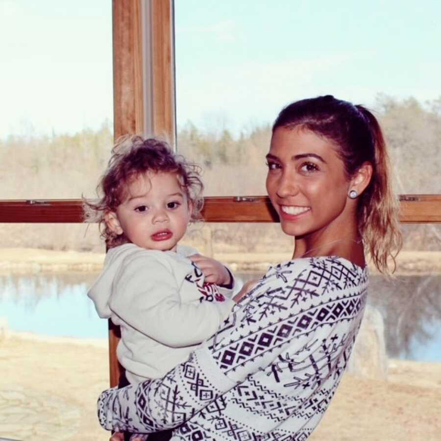 Young mom holds her firstborn son in front of a window with a lake behind them