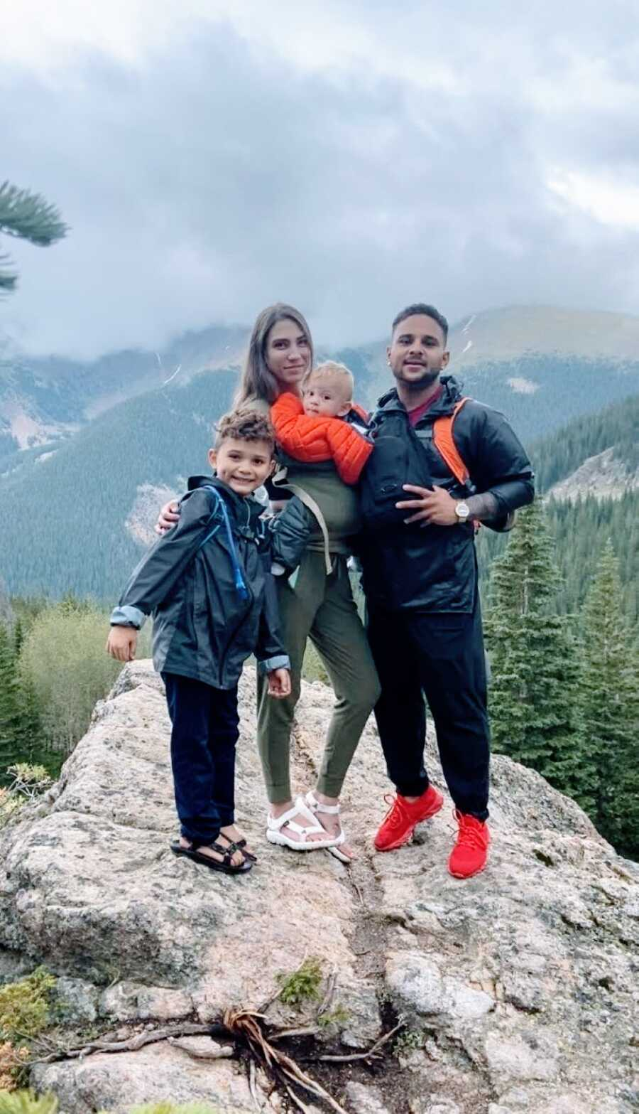 Woman pregnant with her third son poses for a photo with her family while they hike in a mountainous area