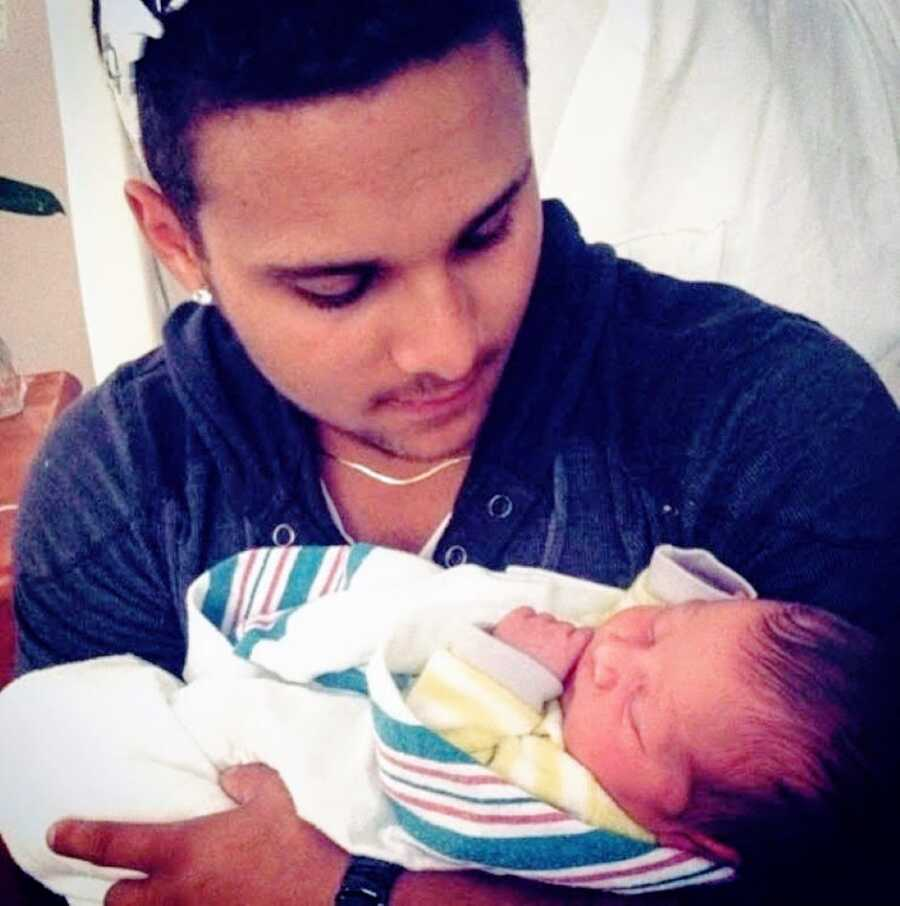 Teen dad holds his newborn son in the hospital