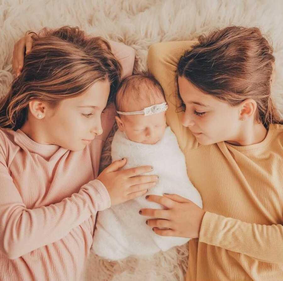 Twin daughters cuddle their newborn baby sister in newborn photoshoot