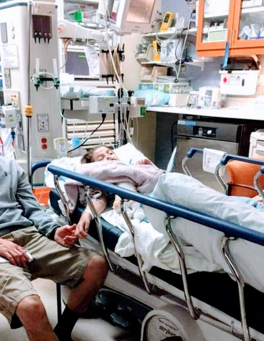 Little girl suffering from a spinal stroke holds her dads hand while waiting results in the hospital