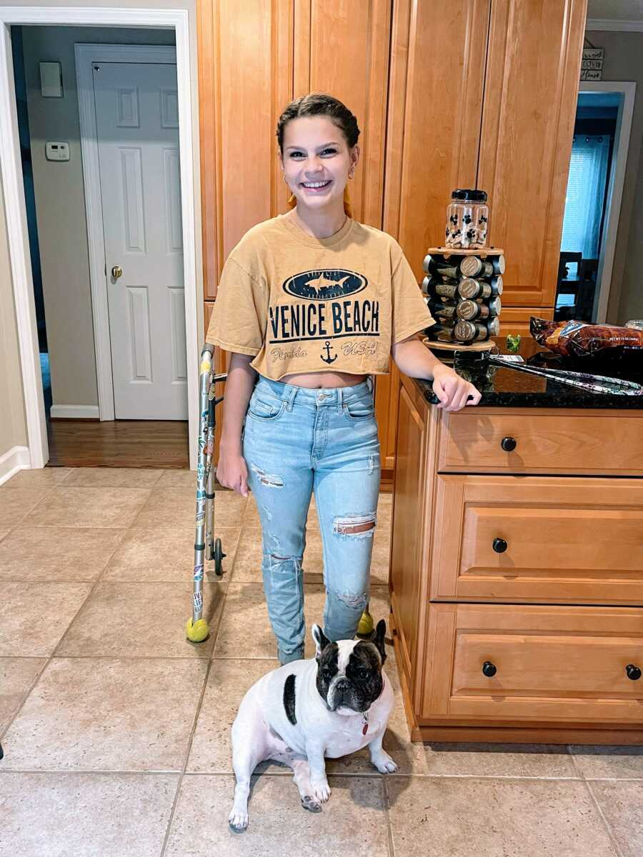 Young teen girl partially paralyzed from a spinal stroke practices walking with a walker in her home
