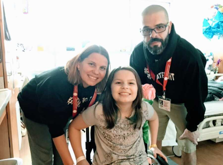 """Parents take a photo with their daughter partially paralyzed due to a spinal stroke while wearing """"FIGHTNATFIGHT sweatshirts"""