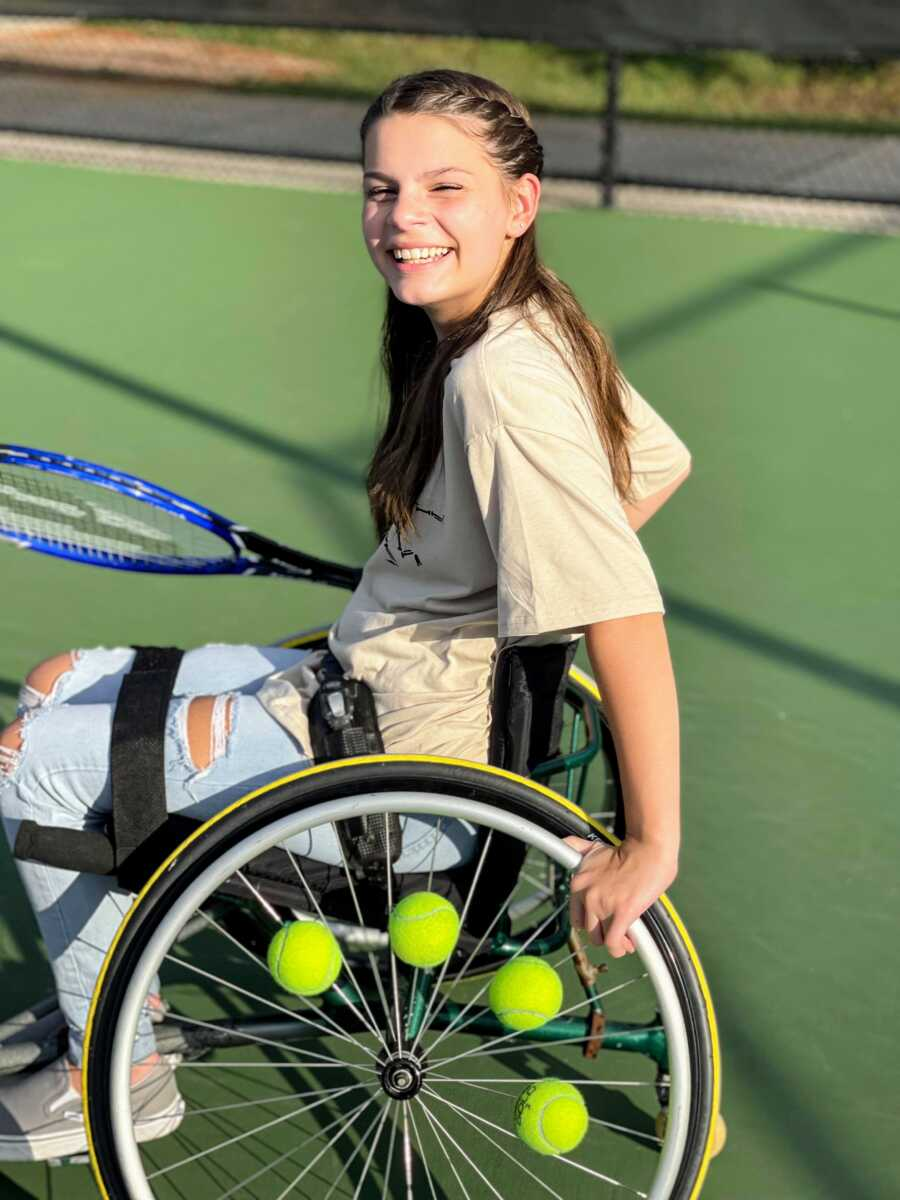 Young girl playing adaptive tennis smiles big while holding a tennis racket