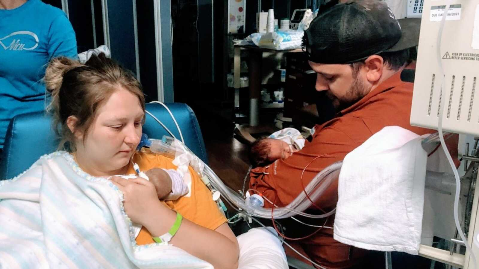 New parents hold their preemie twins while in the NICU
