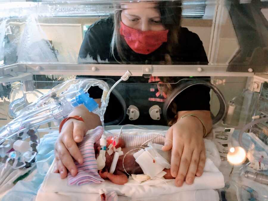 Mom wears a mask while touching her preemie child in the NICU while she's intubated in an isolette