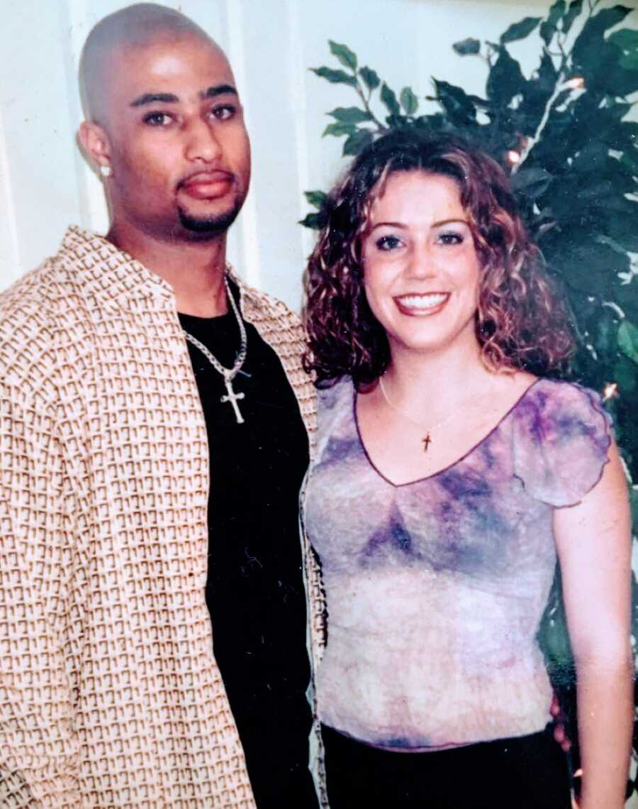 Young interracial couple smile for a photo together in very 90s outfits
