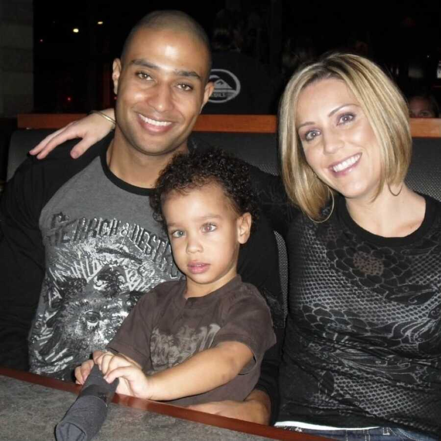 Interracial married couple take a photo out at a restaurant with their special needs son who has Fragile X Syndrome