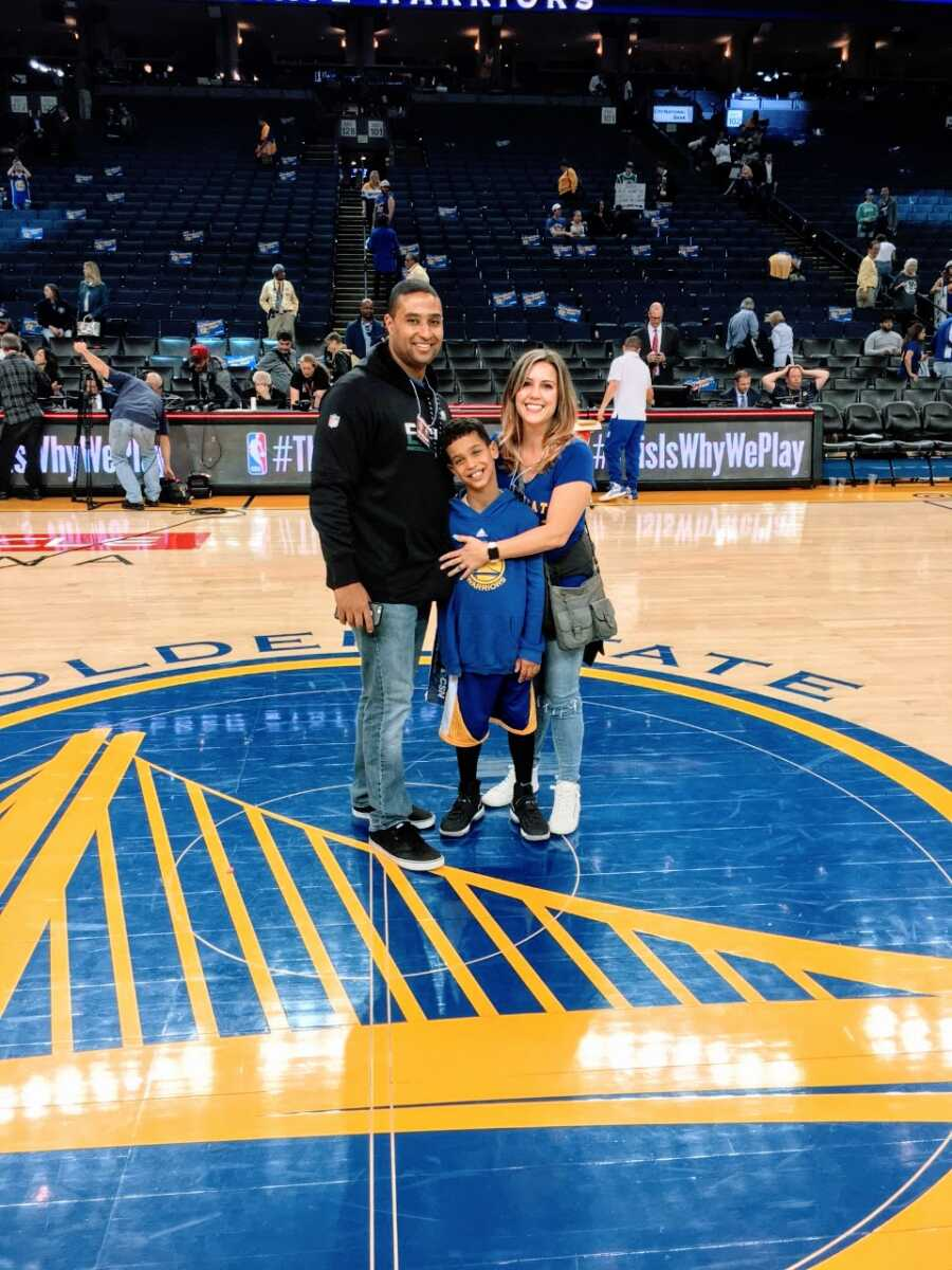 Couple take a photo with their son who has Fragile X Syndrome in the middle of a basketball court