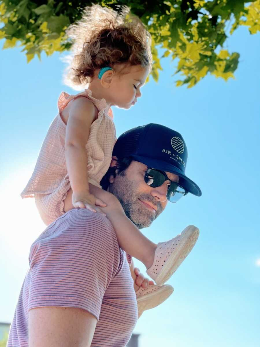 Dad carries his hard of hearing daughter on his shoulders, her blue cochlear implant visible