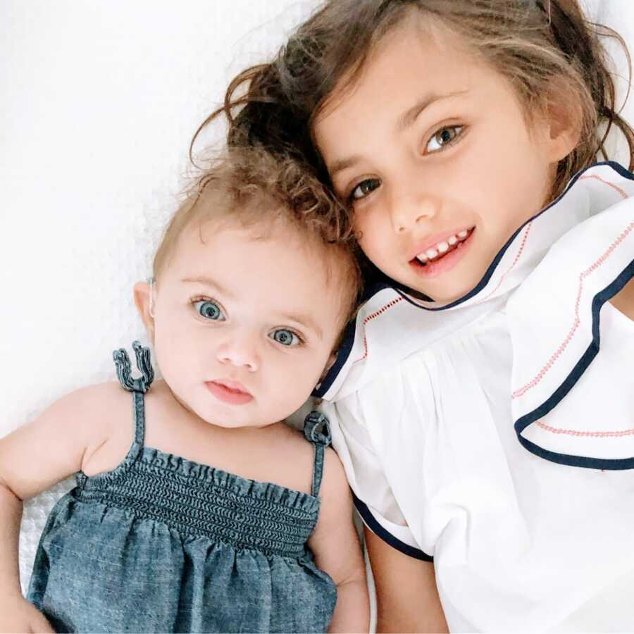 Two sisters spend some bonding time together, one in a white dress and one in a blue denim dress