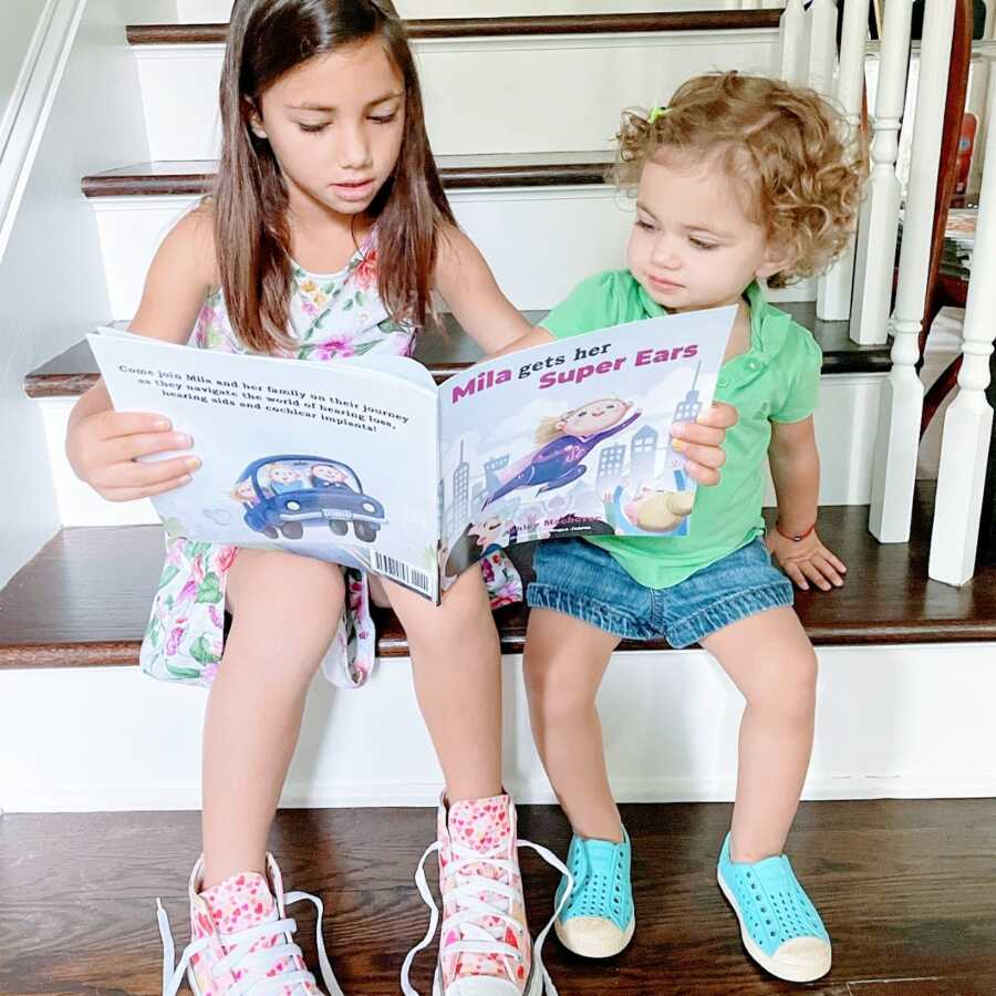 """Big sister reads a book called """"Mila Gets Her Super Ears"""" to her hard of hearing little sister"""
