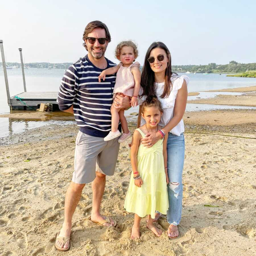 Family of four take a photo together while enjoying some vacation time out at the beach