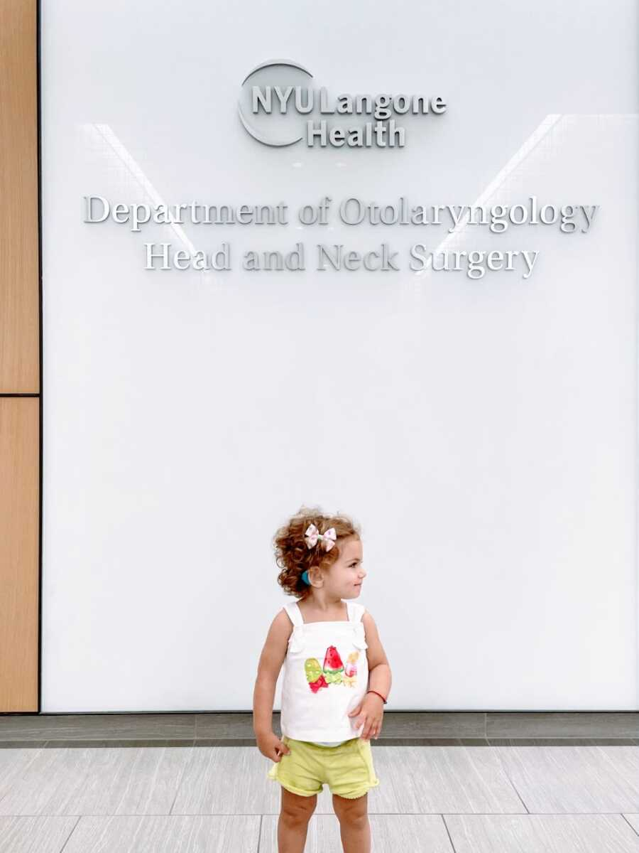 """Little girl poses in front of a sign that reads """"Department of Otolaryngology Head and Neck Surgery"""" with her new cochlear implants"""
