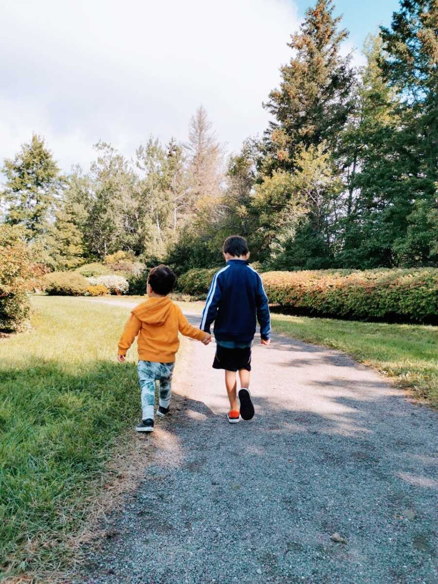 Mom snaps a photo of her two sons walking hand-in-hand during a nature walk