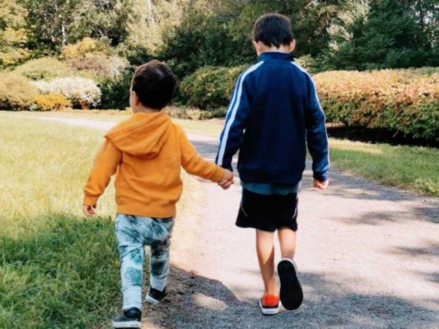 Boy mom takes a photo of her sensitive sons holding each other's hands during a walk