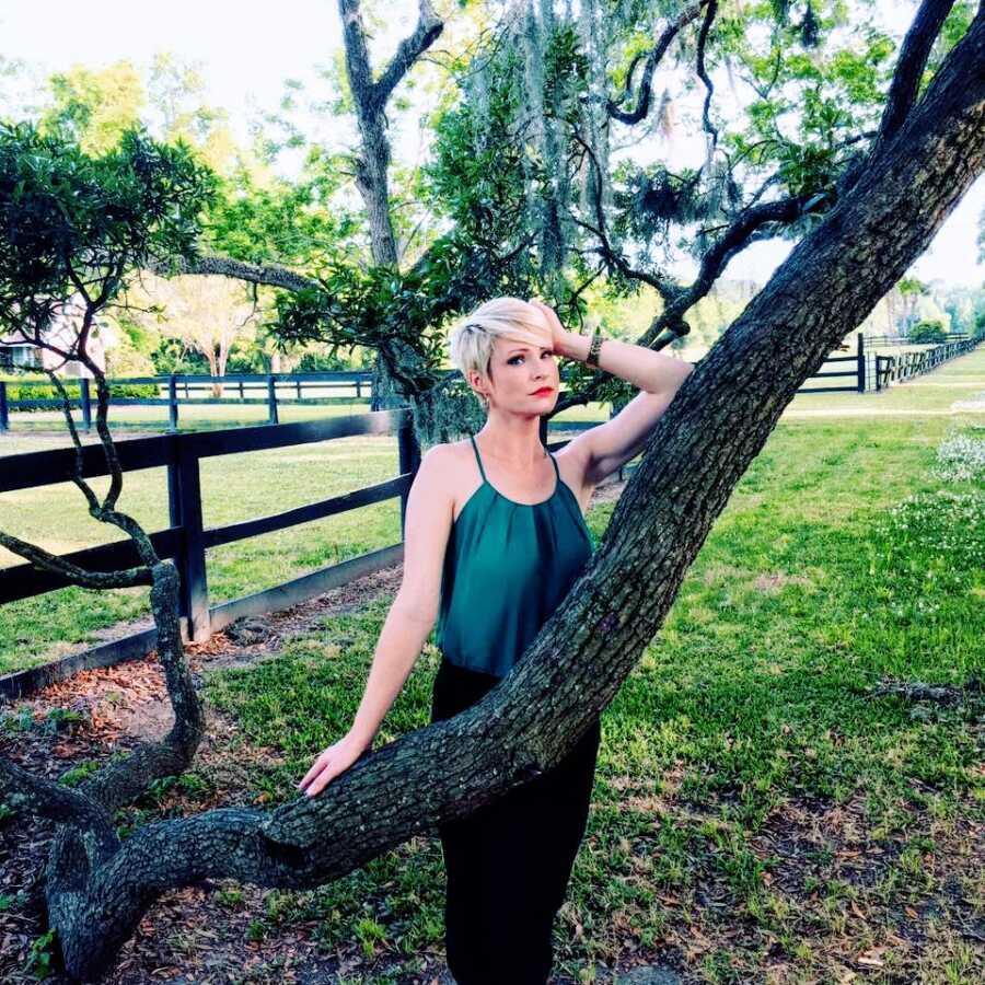 三个孩子的工作妈妈在一棵长满鳞片的树皮树前摆姿势,穿着绿色背心,看起来像一个She-EO