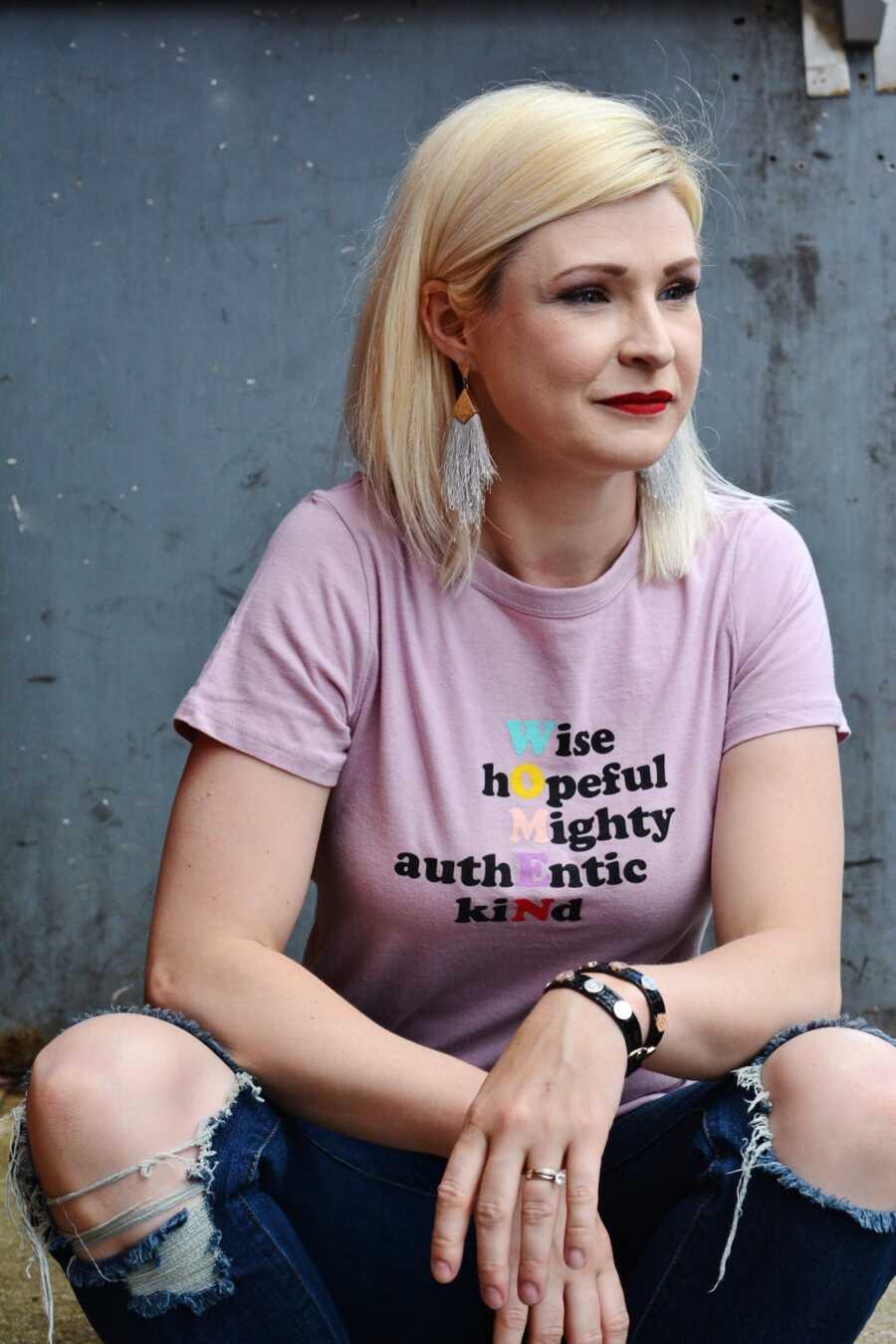 """从母亲精神崩溃中恢复的母亲穿着一件衬衫,上面写着""""女人:智慧、希望、强大、真实、善良"""""""