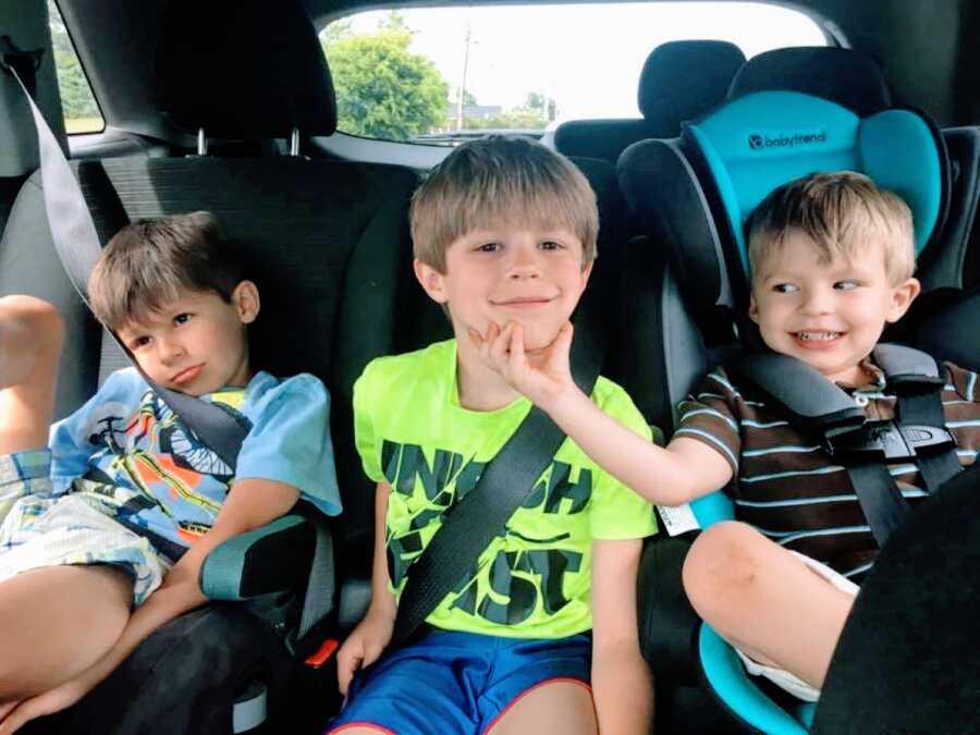 一天早上,在上学的路上,妈妈拍了一张三个儿子坐在车后座上微笑的照片