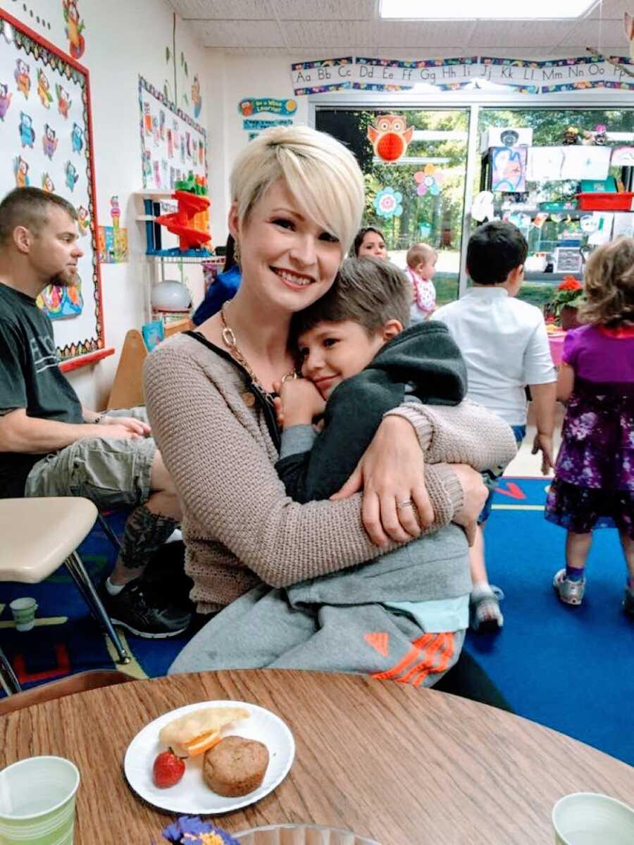 三个孩子的母亲在学校的活动中依偎着她的一个儿子