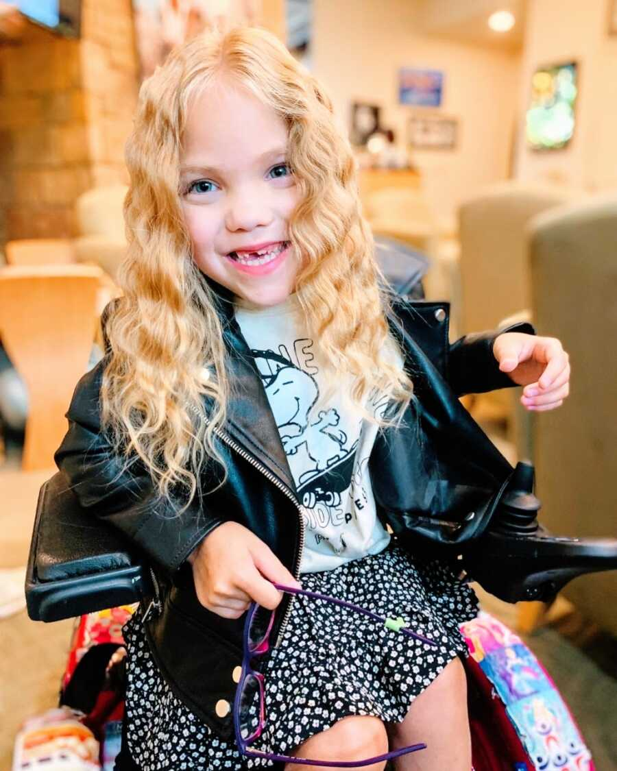 Little girl with cerebral palsy poses for a photo in her wheelchair with her hair curled while wearing a Snoopy shirt and a leather jacket