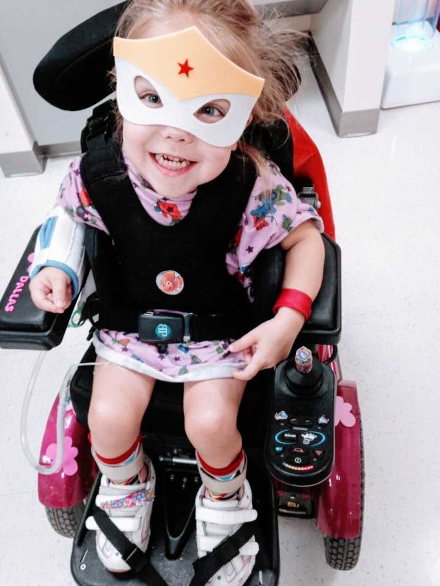 Little girl with cerebral palsy sits in her hot pink motorized wheelchair while wearing a superhero mask