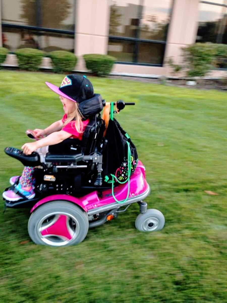 Little girl with cerebral palsy squeals in delight as she zooms by her mom in her hot pink motorized wheelchair