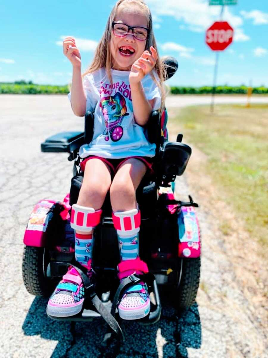 Little girl with cerebral palsy smiles big in her wheelchair during a family outing