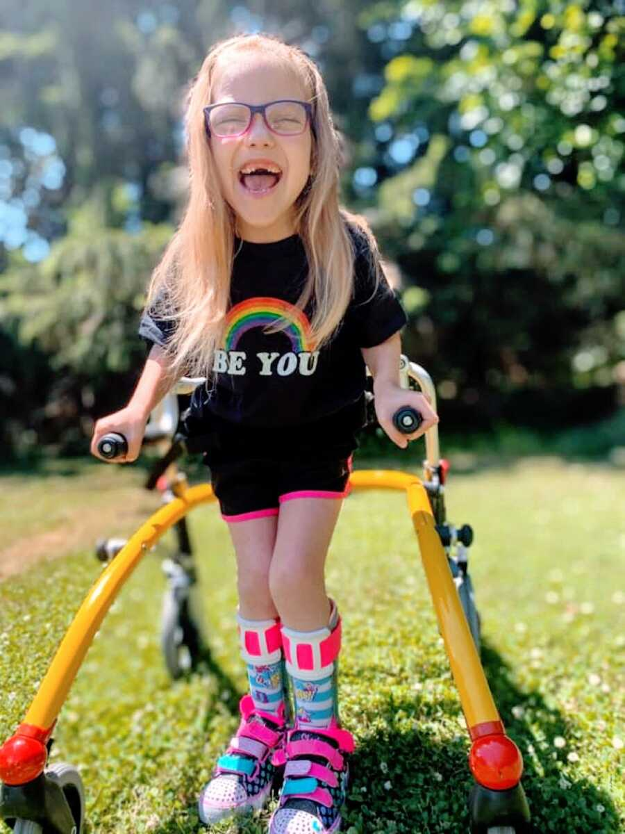"""Little girl with cerebral palsy practices walking with a walker while wearing a shirt with a rainbow on it that says """"Be You"""""""