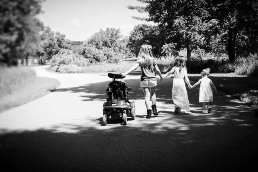 Mom of four girls takes a photo of her daughters walking down the street hand in hand, while one rides in her wheelchair