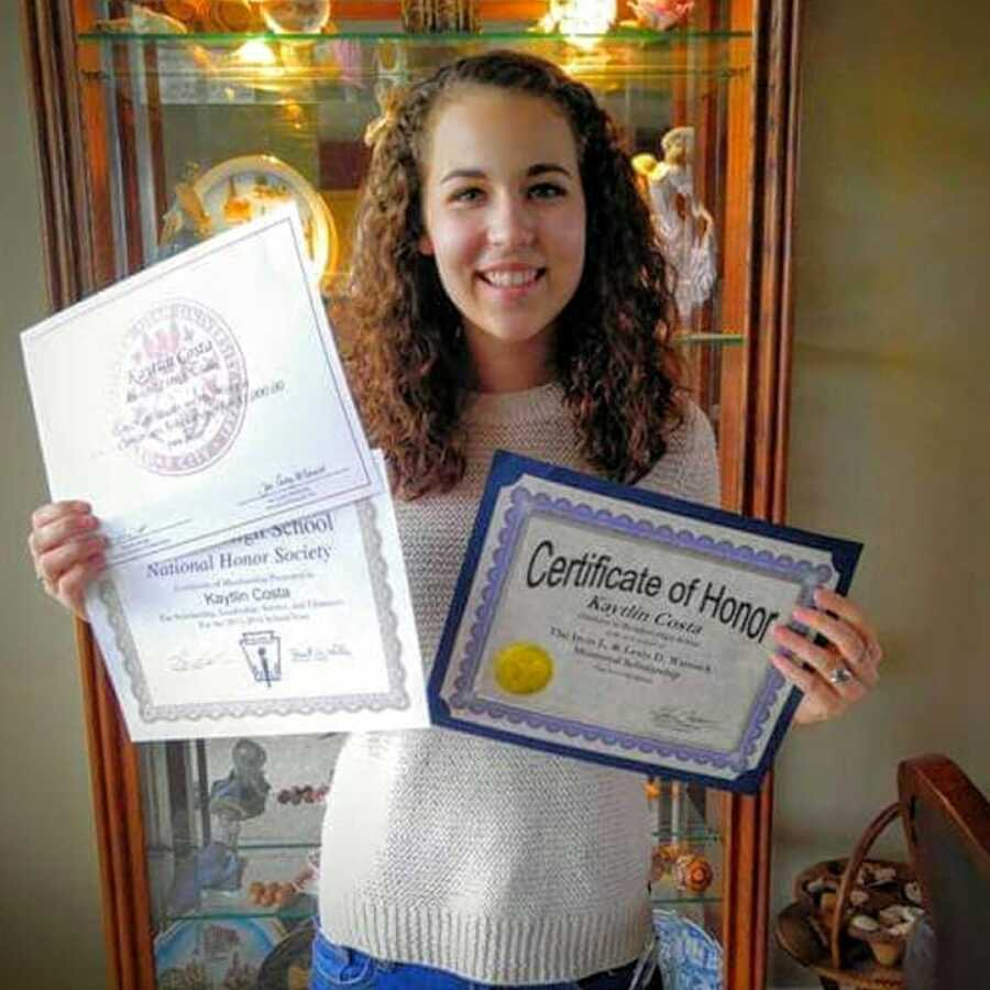 Young teen girl in high school poses with the several honors and awards she won