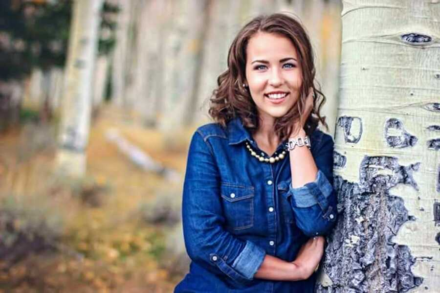Birth mother who now advocates for other birth mothers through the adoption process takes a professional headshot in a blue denim shirt next to a tree