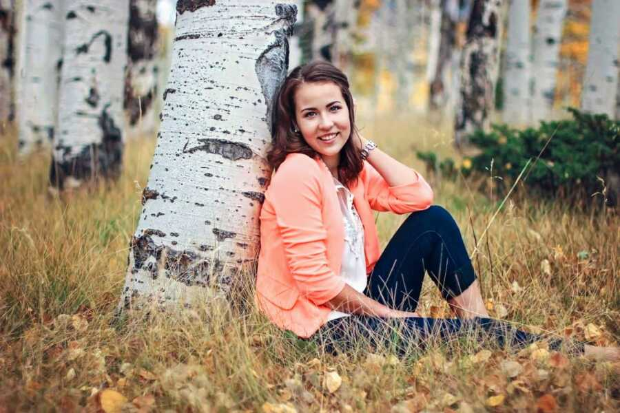 Birth mother sits against a tree trunk while taking professional photos