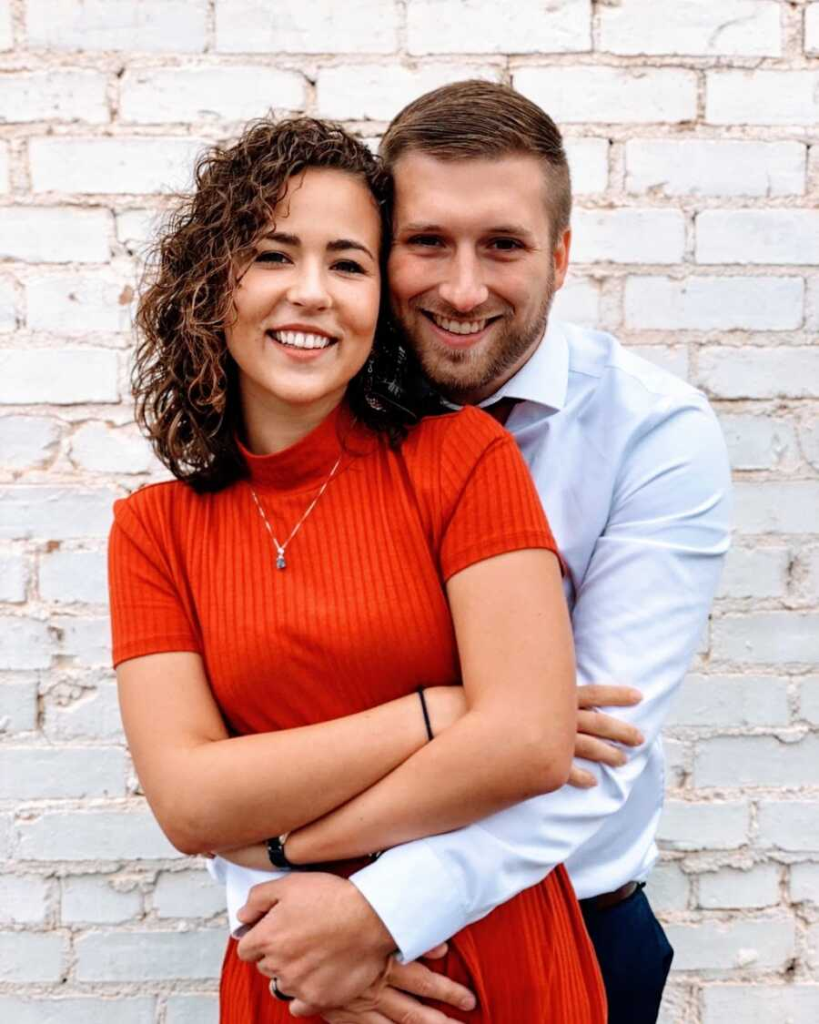 Young engaged couple smile candidly for a photo while embracing