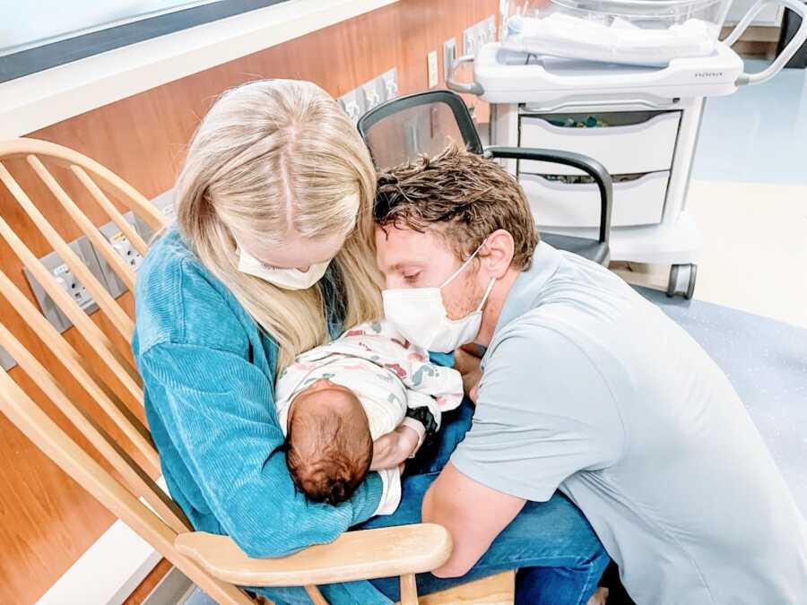 在医院里,一对年轻夫妇抱着一个刚出生的婴儿,敬畏地看着他熟睡
