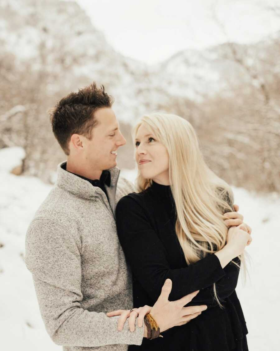 一对年轻的夫妇在一起拍了一张浪漫而亲密的照片,当雪花飘落在他们周围时,他们凝视着对方的眼睛
