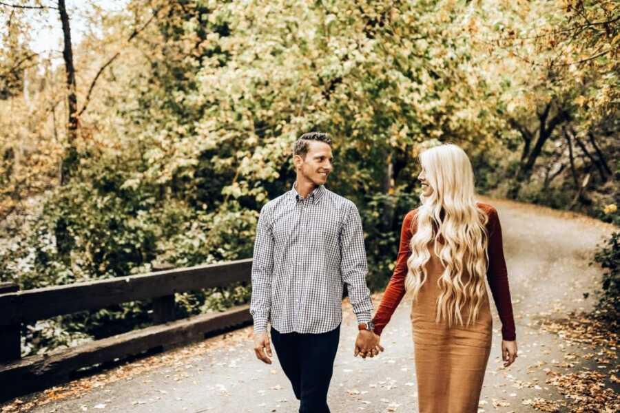 情侣们手牵手走过一座自然桥,拍摄浪漫的秋天主题照片