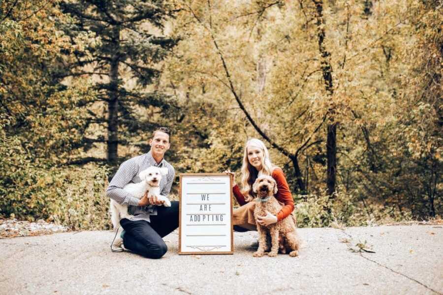 """一对年轻夫妇举着""""我们收养""""的牌子,和他们的两只狗合影留念。"""