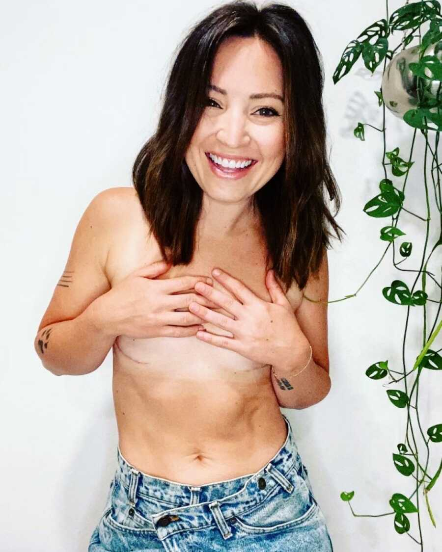 Woman three years cancer free takes a selfie while shirtless, revealing her scars from her double mastectomy