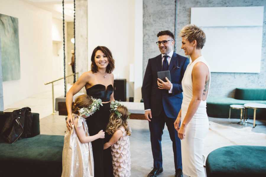 Woman hugs her two daughters while exchanging vows with her new wife