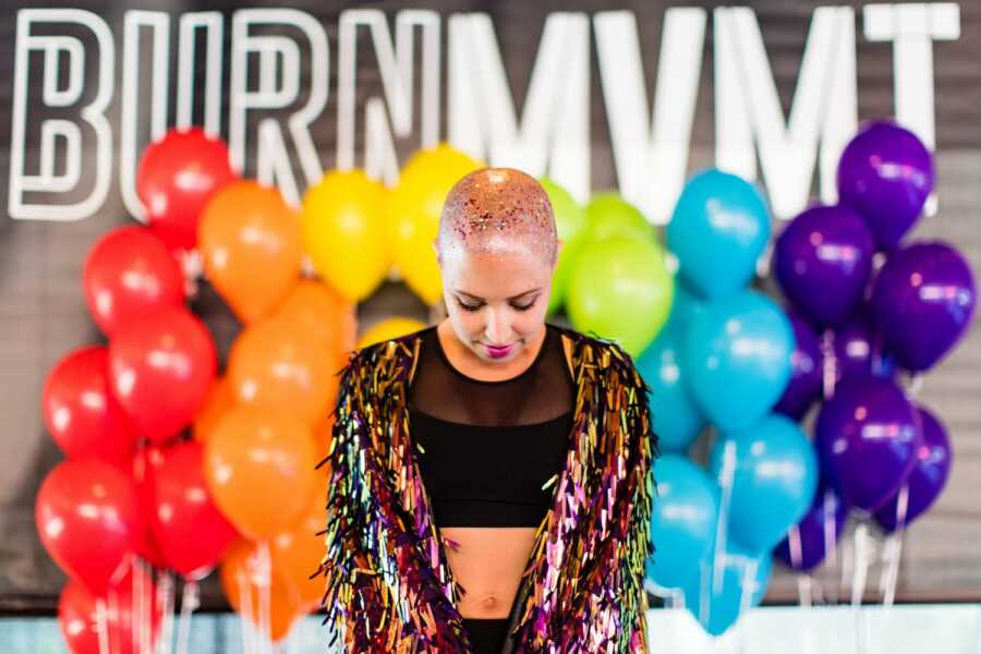 LGBT woman battling breast cancer takes a photo with glitter on her bald head and rainbow balloons behind her