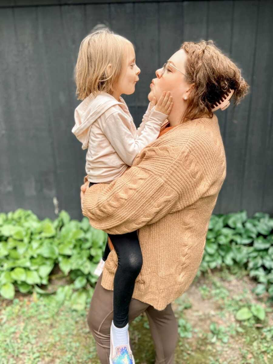 Mom and daughter make kissy faces at each other while taking photos together before school