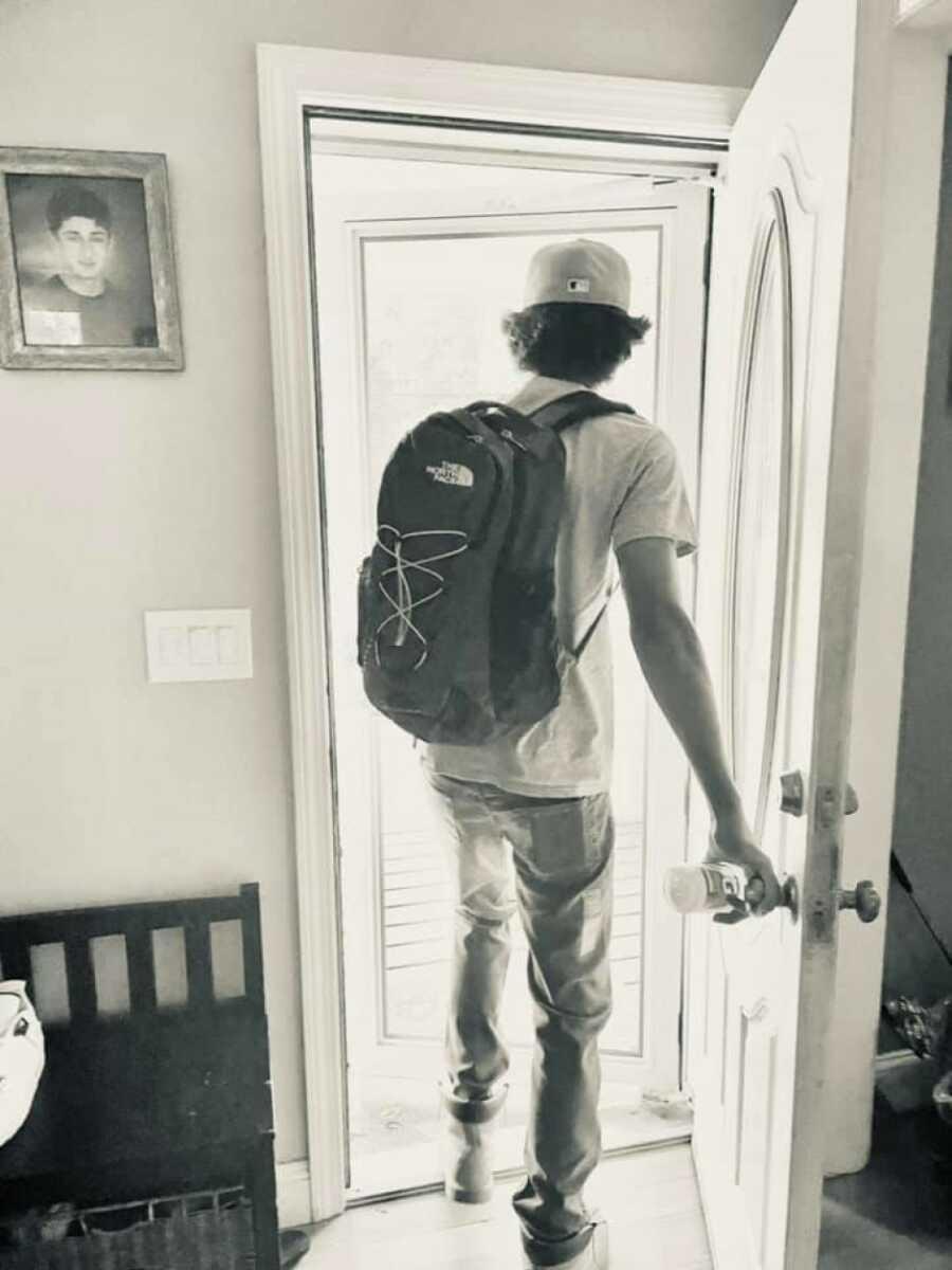 boy walking out of door
