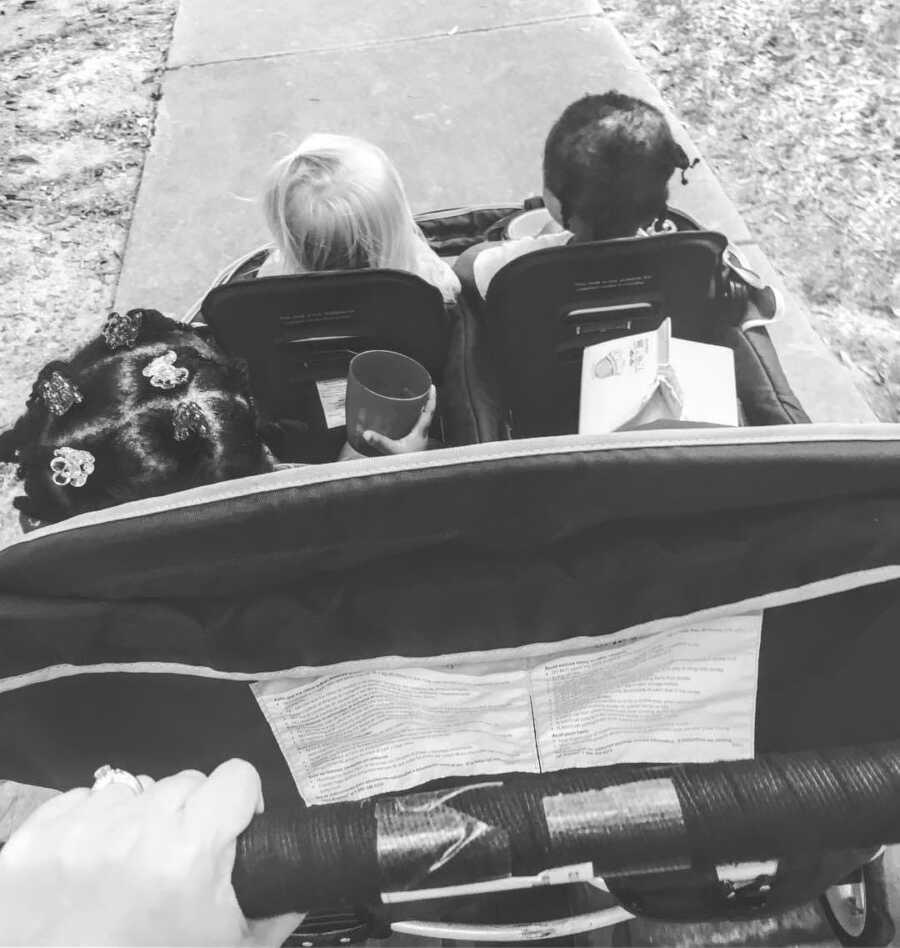 养母把一辆婴儿车推下人行道,车上坐着三个孩子