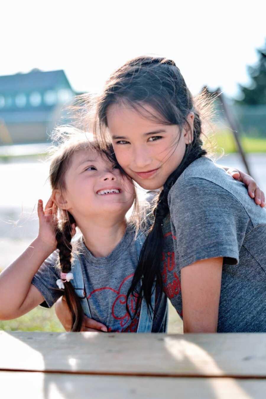 两姐妹穿着相配的衬衫,扎着相配的辫子,微笑着一起拍照