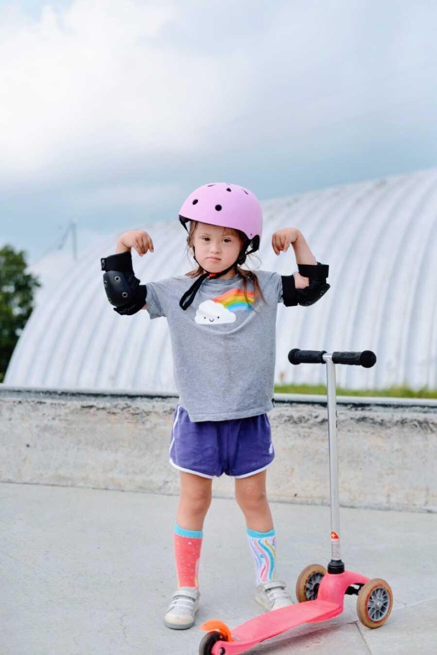 患有唐氏综合症的小女孩戴着头盔和护垫,在摩托车上展示了自己的决心和肌肉