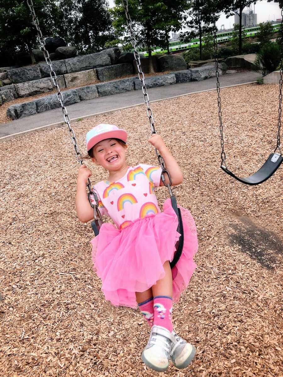 患有唐氏综合症的小女孩在公园荡秋千时笑得很开心,她穿着粉红色的褶边连衣裙,上面有彩虹和心形图案